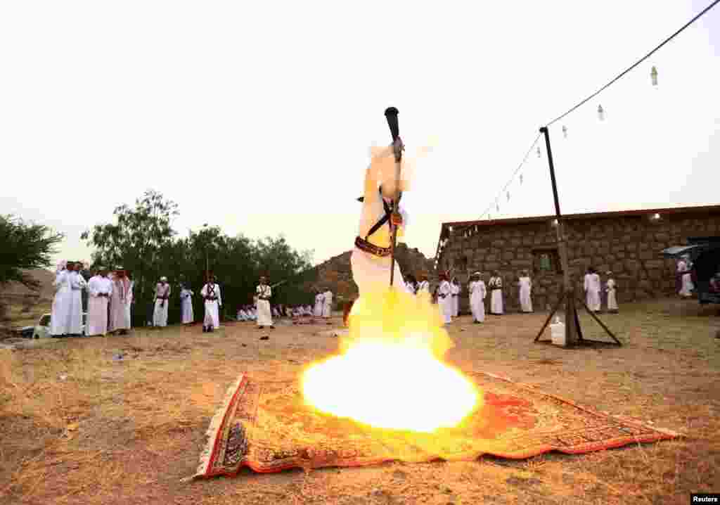 A man fires a weapon as he dances during a traditional excursion near the western Saudi city of Taif, Aug. 8, 2015.
