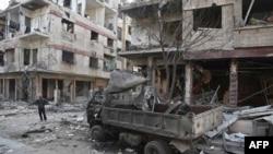 Seorang warga Suriah berdiri di dekat bangunan yang hancur akibat serangan udara di kota Hamouria yang dikuasai pemberontak di kawasan Ghouta Timur, pinggiran ibukota Damaskus, 21 Februari 2018.