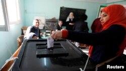 Warga memberikan suaranya dalam referendum konstitusi Mesir di Kairo (14/1).