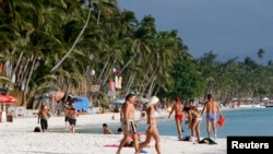 Tourists walk on White Beach on the resort island of Boracay, south of Manila, Feb. 2, 2008.