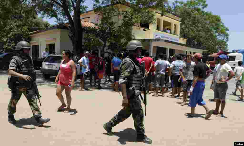 Soldiers patrol near protesters at the customs administration building in the port of Ita Enramada, which is located opposite from the Argentine city of Clorinda, on the outskirts of Asuncion, November 27, 2013.