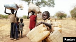 FILE - Children carry belongings as they go to a refugee camp in South Sudan, May 2, 2012. The United Nations refugee agency reports that renewed violence has trapped more than 100,000 residents and refugees in Yei, which now is surrounded by government forces.
