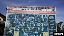 FILE - A police billboard shows individuals — including Santoso, top left — wanted in connection with terrorism cases, in Poso, Central Sulawesi province, Indonesia, Dec. 19, 2015. Development in the province is part of officials' efforts to dissuade would-be terrorists.