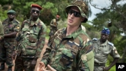 U.S. Army special forces Captain Gregory, 29, from Texas, center, who would only give his first name in accordance with special forces security guidelines, speaks with troops from the Central African Republic and Uganda, in Obo, Central African Republic,