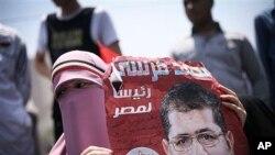 ຊາວອິຢິຍຄົນນຶ່ງ ທີ່ສະໜັບສະໜຸນ ຜູ້ສະໝັກ ພັກສາສະໜາອິສລາມ ທ່ານ Mohammed Morsi ຖືປ້າຍເປັນພາສາ ອາຣັບທີ່ກ່າວວ່າ ທ່ານ Mohammed Morsi ເປັນປະທານາທິບໍດີ ຂອງອີຈິບ.