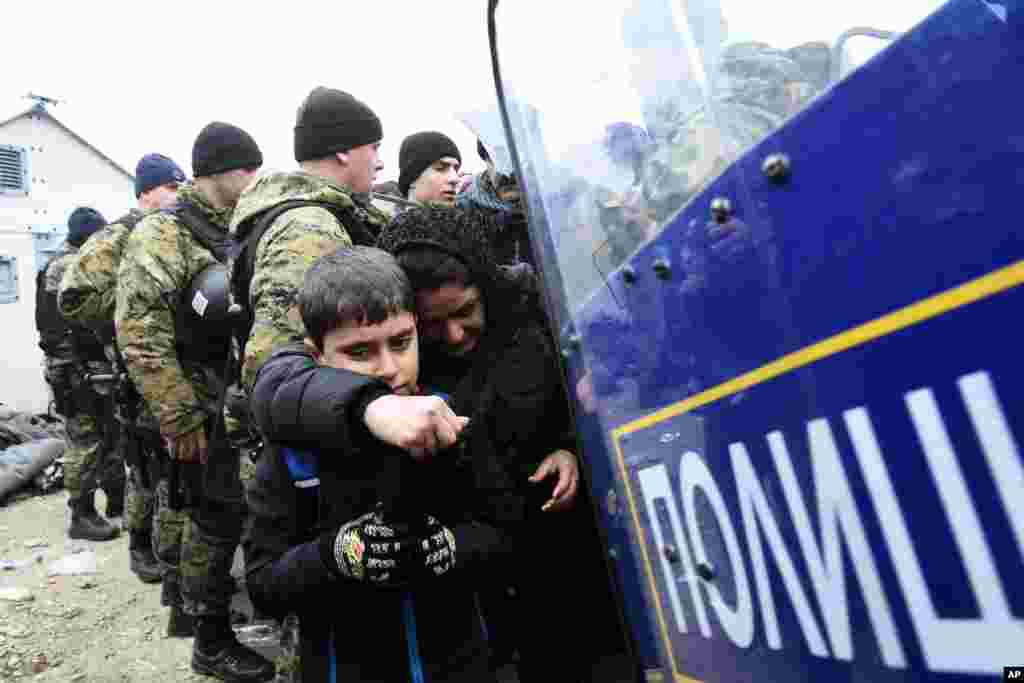 Macedonian policemen stand guard as a woman and a child pass from the northern Greek village of Idomeni to southern Macedonia.