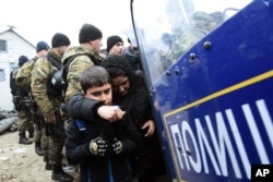 FILE - Macedonian policemen stand guard as a woman and a kid pass from the northern Greek village of Idomeni to southern Macedonia, Nov. 20, 2015.