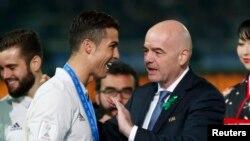 Le président de la Fifa, Gianni Infantino, à droite, congratule Cristiano Ronaldo de Real Madrid lors de la remise du trophée de la coupe du monde des clubs au stade Yokohama, Japon, 12 décembre 2016.