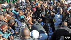 Thousands of young students and their parents push their way into the gates causing a stampede at the University of Johannesburg, South Africa, Tuesday Jan. 10, 2012. Prospective students stampeded at the gate of a university Tuesday, leaving one person d