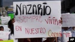 """Čovek drži transparent na kojem piše: """"Nazario će uvek živeti u našim srcima."""""""