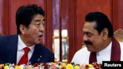 Japan's Prime Minister Shinzo Abe (L) talks with Sri Lankan President Mahinda Rajapaksa during their bilateral meeting at the President Secretariat after in Colombo, September 7, 2014.