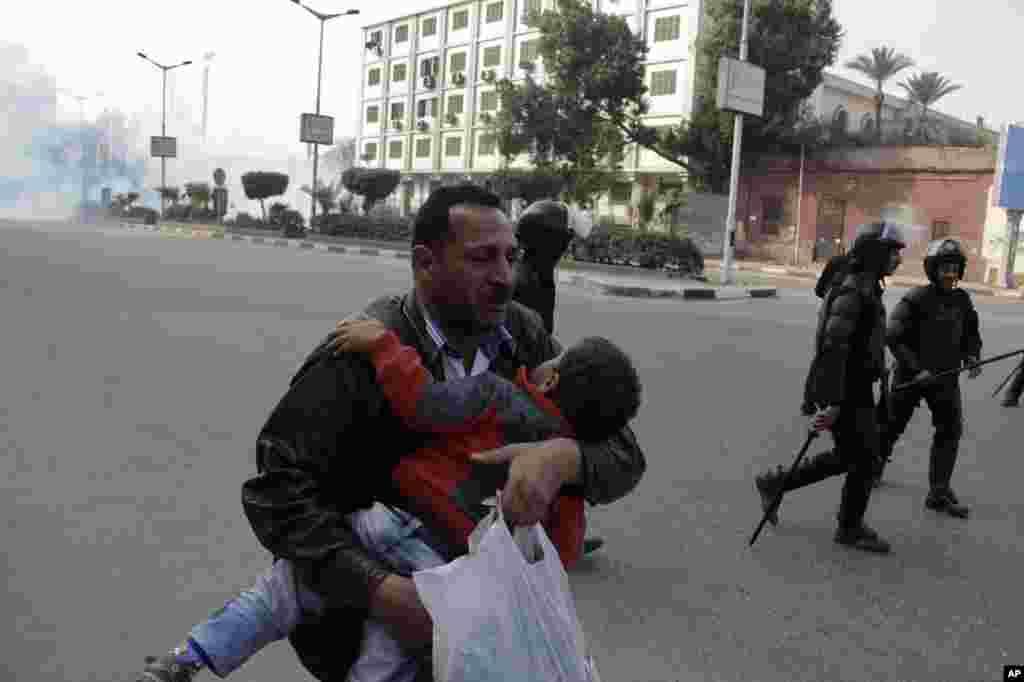Một người đàn ông bồng con chạy tránh hơi cay trong vụ xung đột giữa lực lượng an ninh Ai Cập và những người ủng hộ Tổng thống bị lật đổ Mohamed Morsi tại Cairo. Những người ủng hộ ông Morsi thỉnh thoảng tổ chức những cuộc biểu tình chống trưng cầu dân ý về hiến pháp trong tuần này.