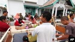 Korban gempa di Aceh menerima perawatan medis di luar puskesmas di kabupaten Bener Meriah (2/7). (AP/Ahmad Ariska)
