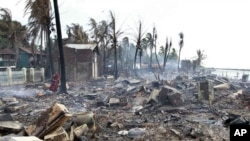 A Buddhist monk stands in the debris of burned houses still smoldering in Sittwe, Burma, Monday, June 11, 2012.