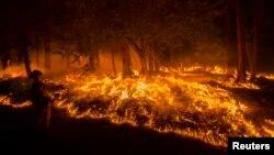 Un bombero lanza agua para contener las llamas en Fresh Pond, California donde arrasa el incendio King.