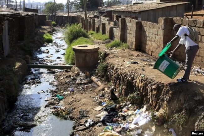 FILE - A student empties a dustbin next to a murky stream near a school in Kenya's Kibera slums in capital Nairobi, Sept. 21, 2015.