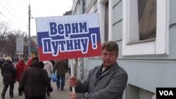 俄罗斯吞并克里米亚后,当局去年3月在莫斯科组织亲政府支持普京集会游行。普京的一名支持者手举标语:我们信任普京。(美国之音白桦拍摄)
