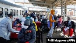 Des patients s'inscrivent à l'extérieur de la clinique mobile du train Transnet-Phelophepa pour recevoir des soins de santé à la gare de Dube à Soweto, le 22 juin 2021.