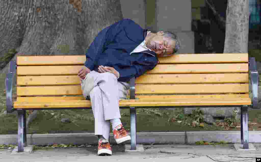 A man takes a nap on a bench at a park in Tokyo, Japan.