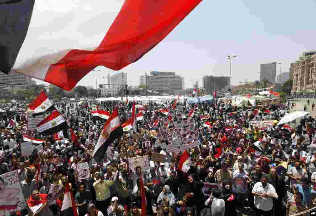 Opponents of Egypt's Islamist President Mohamed Morsi wave national flags in Tahrir Square in Cairo, June 28, 2013.