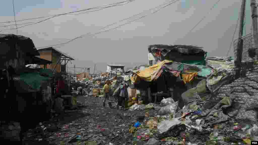 Junk shops line this intersection where scavengers drop off and haul away bags of recyclable material at the Smokey Mountain dump site, Manila Bay, Philippines, Dec. 12, 2013. (Simone Orendain for VOA)