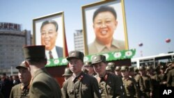 North Korean soldiers walk in the Ryomyong residential area, a collection of more than a dozen apartment buildings, after attending its official opening ceremony, while portraits of the late leaders Kim Il Sung and Kim Jong Il are seen on April 13, 2017.