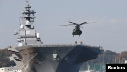 A helicopter lands on the Izumo, Japan Maritime Self Defense Force's (JMSDF) helicopter carrier.