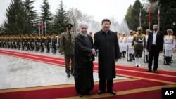 Presiden China Xi Jinping (tengah kanan) berjabat tangan dengan Presiden Iran Hassan Rouhani setibanya di istana e Saadabad, Tehrran, Iran (23/1).