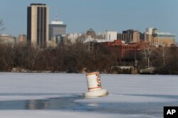 A buoy is encased in ice and snow along the James River near downtown Richmond, Va., Jan. 5, 2018. A winter storm swept through the area Thursday dumping several inches of snow. Bitter cold is expected through the weekend.
