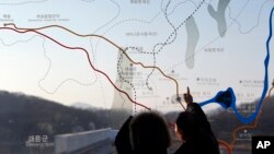 People look at a map of the border area between North and South Koreas at the Imjingak Pavilion near the border village of Panmunjom, which has separated the two Koreas since the Korean War, in Paju, north of Seoul, South Korea, Monday, Jan. 11, 2016.