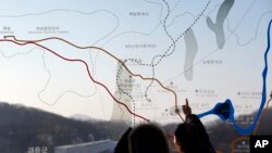 FILE - People look at a map of the border area between North and South Koreas at the Imjingak Pavilion near the border village of Panmunjom, which has separated the two Koreas since the Korean War, in Paju, north of Seoul, South Korea, Monday, Jan. 11, 2016.