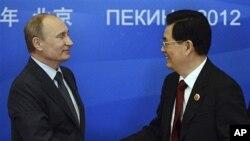 상하이협력기구 정상회의에서 악수하는 푸틴 러시아 대통령(왼쪽)과 후진타오 중국 국가주석.