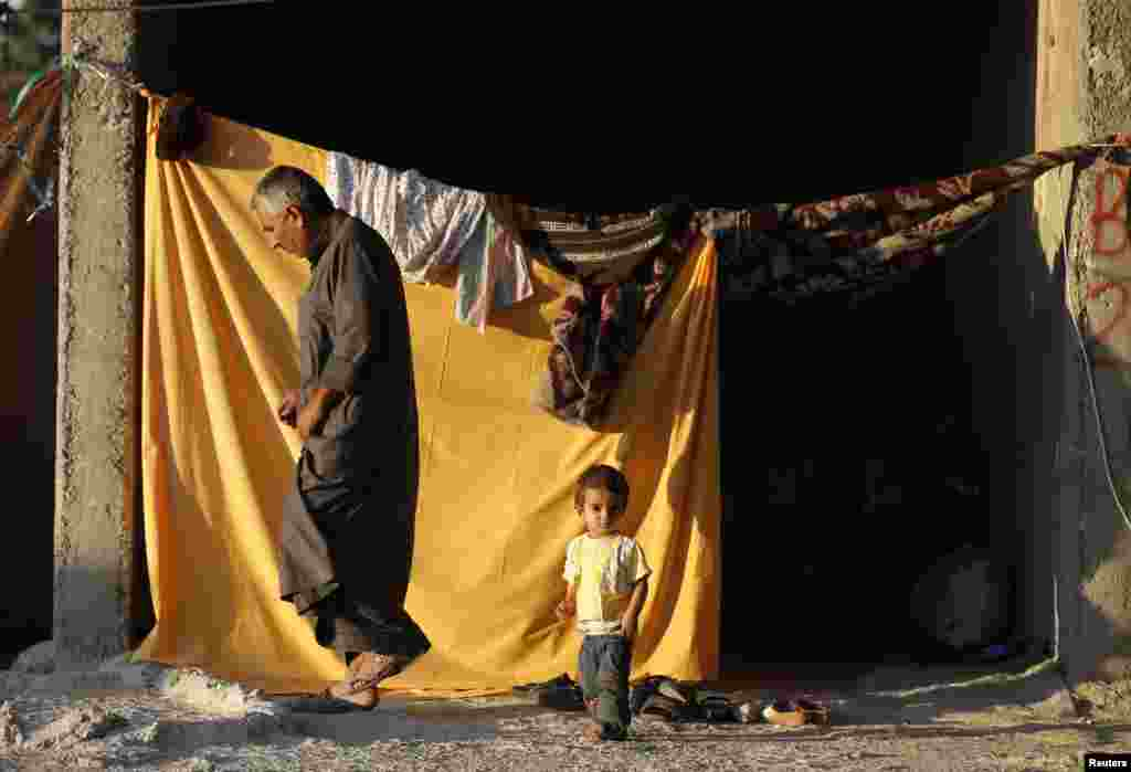 A Kurdish refugee and his child stand at the entrance of their temporary shelter in a refugee camp in the southeastern town of Suruc, Sanliurfa province, Oct. 5, 2014.