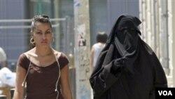 Dua perempuan Perancis di jalanan Paris. Larangan penggunaan burka di tempat umum mulai berlaku secara resmi 11 April ini.