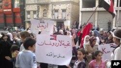 ພວກແມ່ຍິງແລະເດັກນ້ອຍ ຖືປ້າຍປະທ້ວງ ປະທານາທິບໍດີຊີເຣຍ ທ່ານ Bashar Assad ທີ່ເມືອງທ່າ Banias (3 ພຶດສະພາ 2011)