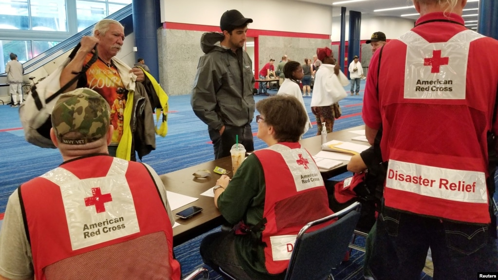 Evacuees arrive to seek shelter with Red Cross volunteers at the George Brown convention center after