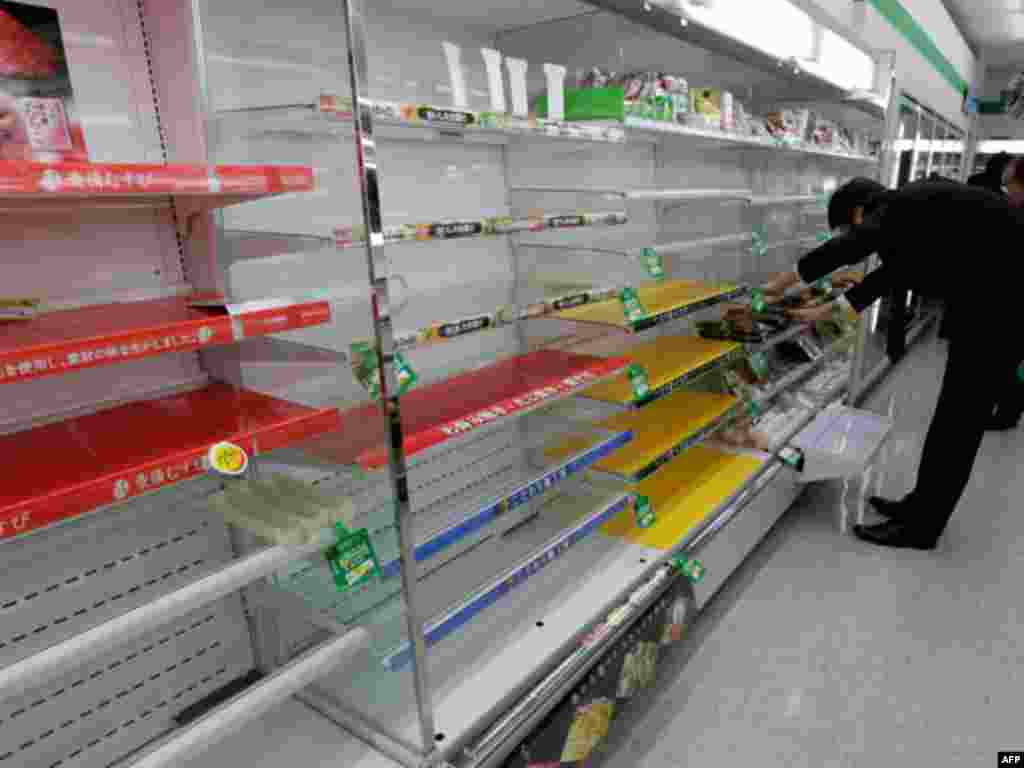 A man looks for supplies in a store in Tokyo that has almost sold out of food and drink as people are unable to return home after an earthquake March 11, 2011.