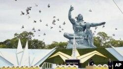 Burung merpati beterbangan di sekitar Patung Perdamaian, pada peringatan 74 tahun jatuhnya bom atom yang menandai berakhirnya Perang Dunia II, di Taman Perdamaian Nagasaki, selatan Jepang, 9 Agustus 2019. (Kyodo News via AP)