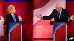 Democratic presidential candidate Sen. Bernie Sanders, right, gestures toward former Secretary of State Hillary Clinton during a democratic presidential primary debate at the Gaillard Center, in Charleston, S.C., Jan. 17, 2016.