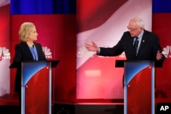 Democratic presidential candidate Sen. Bernie Sanders, right, gestures toward former Secretary of State Hillary Clinton during a democratic presidential primary debate at the Gaillard Center, in Charleston, S.C., Jan. 17, 2016.