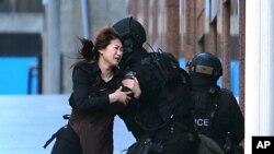 Seorang sandera berlari ke arah polisi setelah melarikan diri dari penyanderaan di kafe di distrik bisnis Martin Place, Sydney, Australia (15/12). (AP/Rob Griffith)