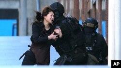 Une femme parvient à s'échapper d'un café à Sydney en Australie, où un homme armé a pris plusieurs personnes en otage, le 15 décembre 2014. (AP Photo/Rob Griffith)