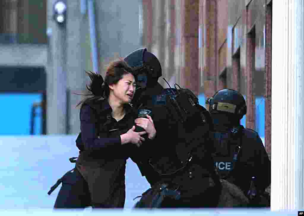 A hostage runs to armed tactical response police officers for safety after she escaped from a cafe under siege at Martin Place in the central business district of Sydney, Australia.