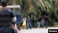 Cảnh sát Malaysia bắt 2 người đang ra khỏi ngôi làng, gần khu vực Kampung Tanduo, nơi binh sĩ Malaysia đột kích vào trại của nhóm người Philippines võ trang