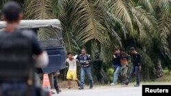 Polisi Malaysia menahan dua orang yang keluar dari Tanjung Labian, sebuah desa dekat Kampung Tanduo, Rabu (6/3). Tentara Malaysia bentrok dengan kelompok bersenjata Filipina di wilayah tersebut, Selasa (5/3).