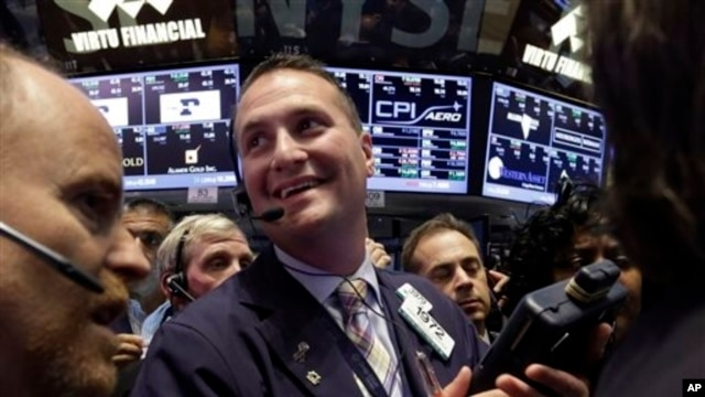 FILE - Trader Jonathan Corpina, center, smiles as he works on the floor of the New York Stock Exchange, June 21, 2013.