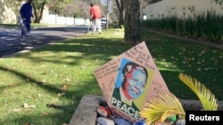 Gardeners clean the lawn as a get well card is placed outside the house of former President of South Africa Nelson Mandela in Houghton, June 10, 2013.