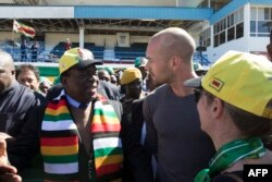 FILE: Zimbabwean President Emmerson Mnangagwa greets people after addresses a meeting attended by farmers and businessmen from the Zimbabwean White community ahead of this month's elections on July 21, 2018 in Harare.