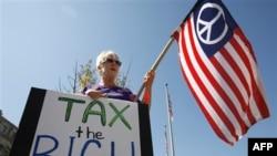 """Učesnica protesta u Vašingtonu sa natpisom """"Oporezujte bogate"""", 6. oktobar 2011."""