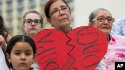 Angela Reyes holds a sign while participating in a vigil at the Governor's Mansion in Austin, Texas, Thursday, in response to the Supreme Court decision about President Obama's immigration executive order. (Jay Janner/Austin American-Statesman via AP)